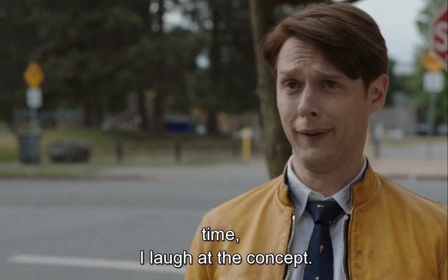 A still shot of the character Dirk Gently from the BBC America series 'Dirk Gently's Holistic Detective Agency' - a young white man with reddish hair, wearing a yellow jacket, a blue tie and a white shirt - is in sharp focus against a blurred background of a park. The closed captioning below him reads 'time, I laugh at the concept.'