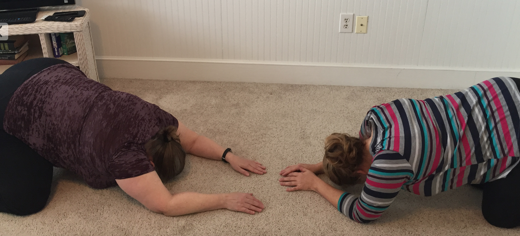 Me and my sister in child's pose, arms in front in variations.