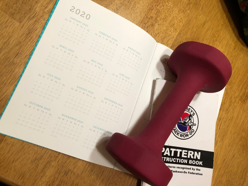 A 2020 calendar printed on white paper sits on a wooden table top. There is a dark pink weight and a taekwondo reference booklet resting on the calendar.