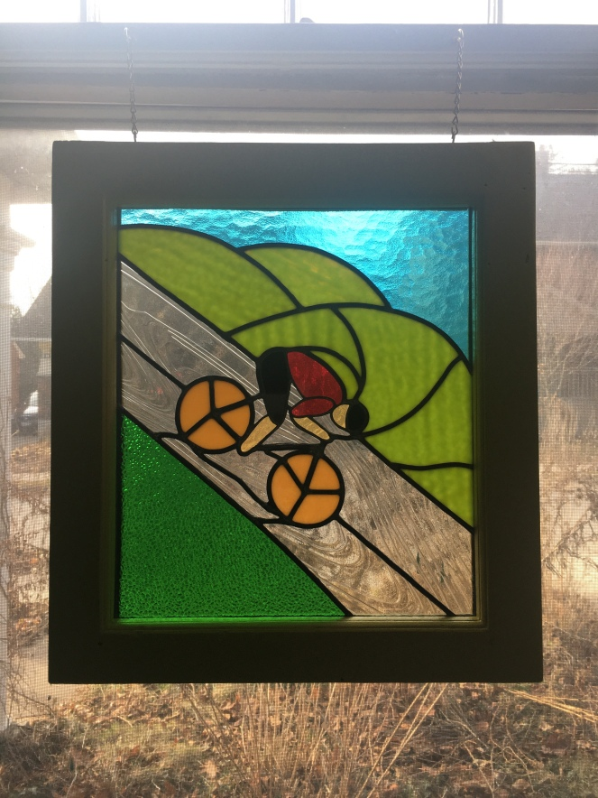 A small stain glass peice of art shows a cyclist speeding down a steep hillside.