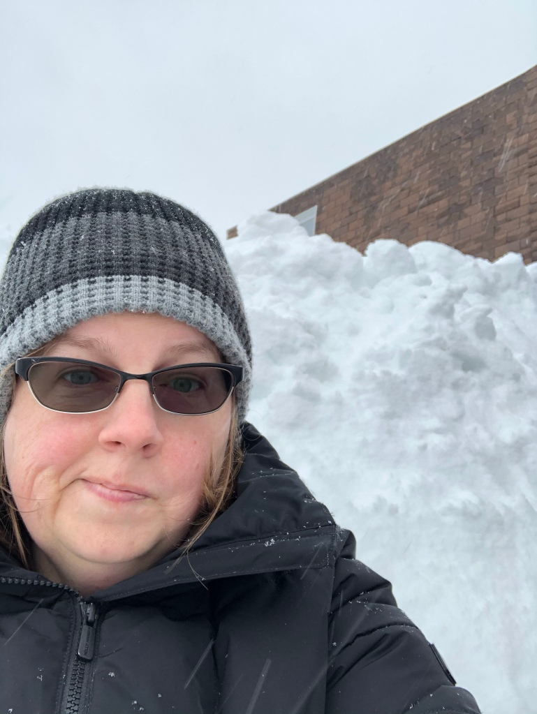 The author, a white woman  wearing a black and grey winter hat and a black jacket stands in front of a towering snowbank. A corner of a brown mansard roof can be seen in the background.