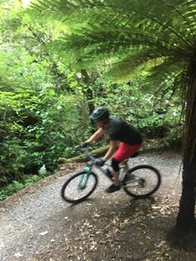The same subject as above riding a turquoise mountain bike. The rider is wearing a black knee brace, berry-coloured shorts, and a grey shirt and helmet. She is rounding a bend on a gravel and dirt trail, and is surrounded by ferns.