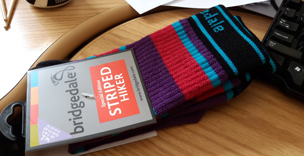 "A pair of hiking socks still in the package. The socks have thick black, purple, dark pink, and turquoise stripes. The brand name ""Bridgedale"" is partially visible on the cuff of the socks. The tag is grey and reads ""Bridgedale Special Edition Striped Hiker."""