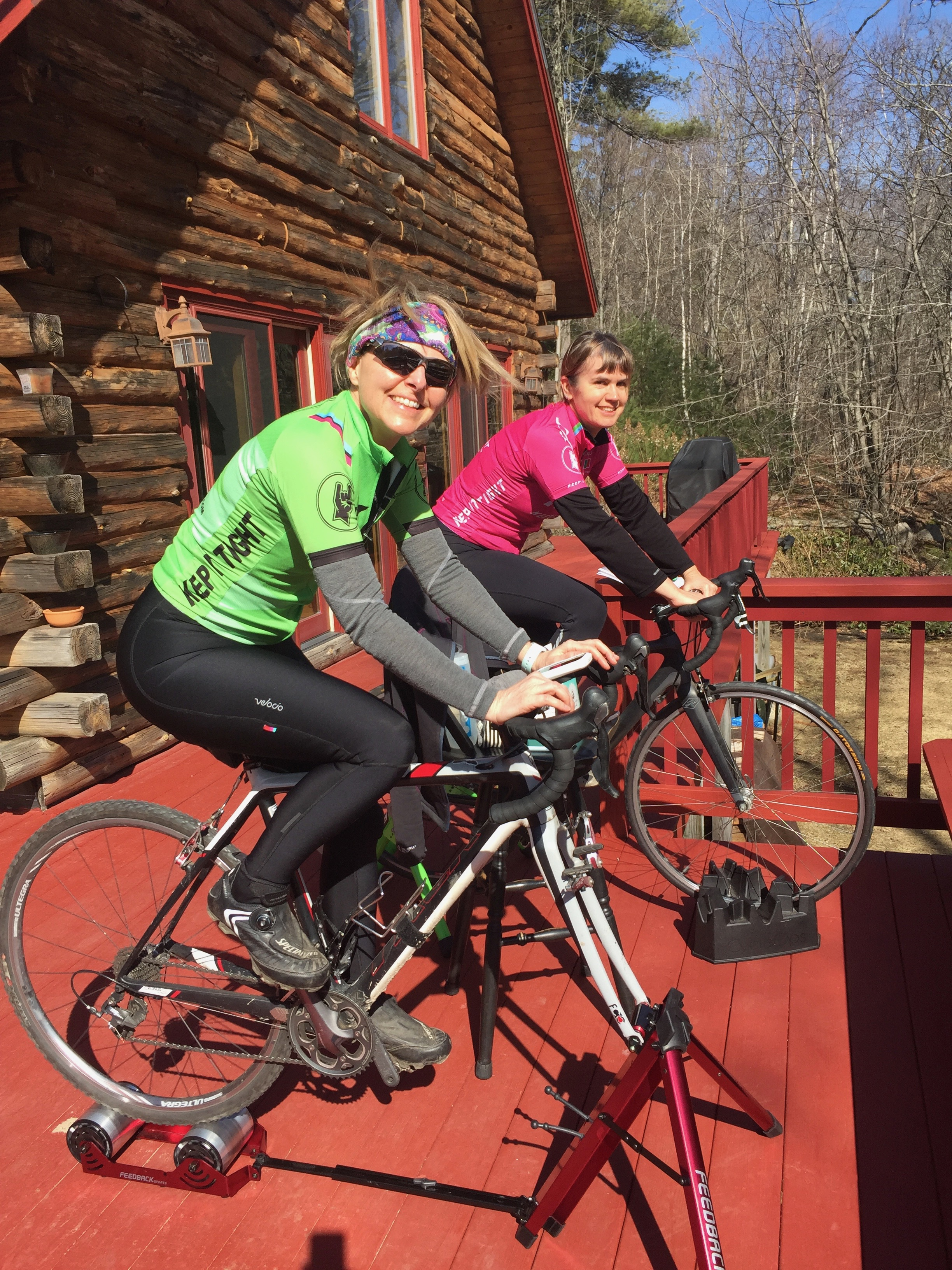 Michele and Rachel, smiling and pedaling on their trainers on the cold but sunny deck.