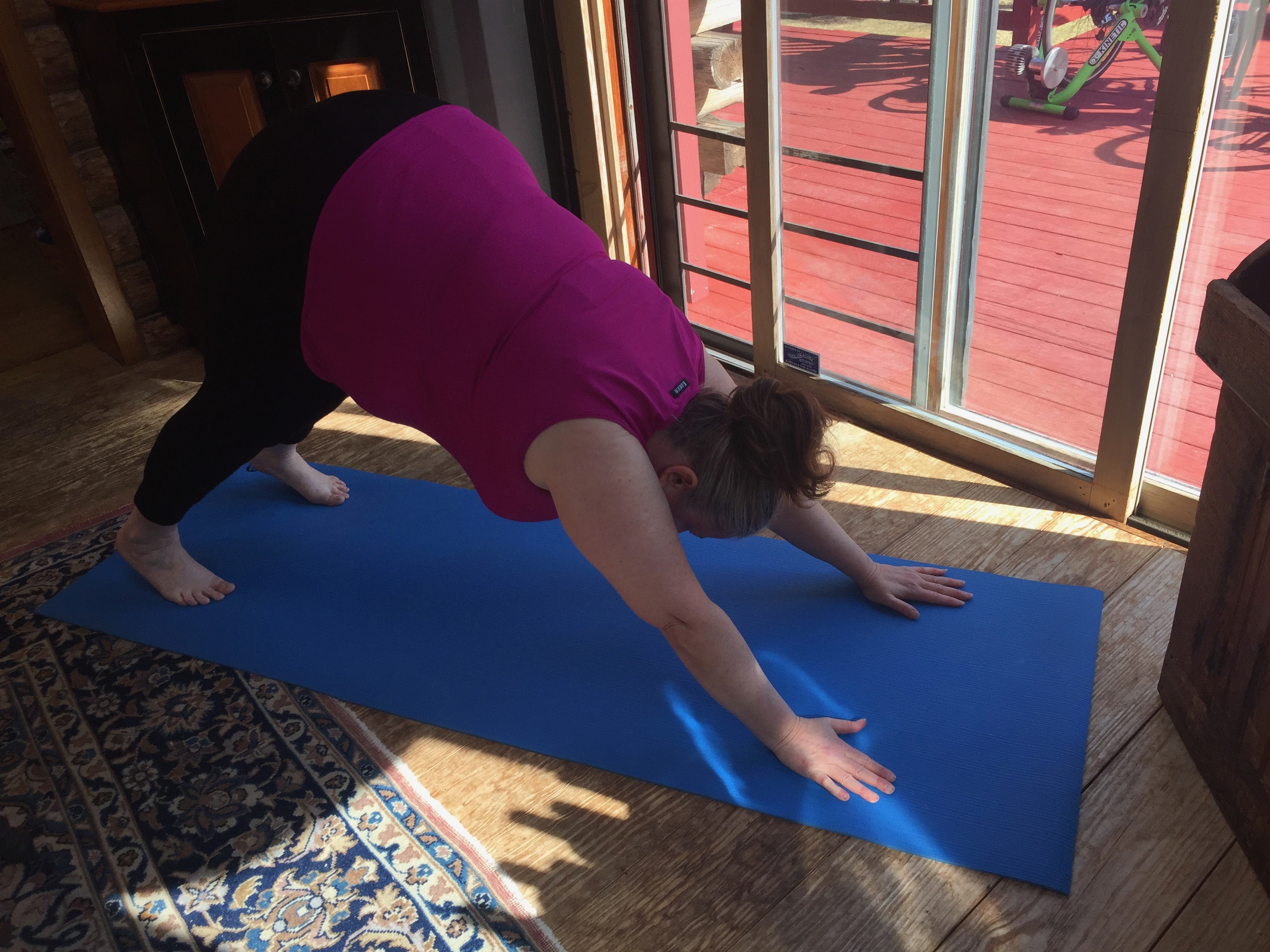Me in downward facing dog on my mat inside the house.