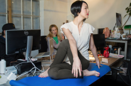 A person doing yoga on their desk at work. This person got their work/yoga boundaries confused here.