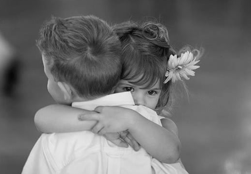 Innocent picture of one child hugging and soothing another. Additional soothing provided by soft-focus black and white image, and flower in hair of one child.