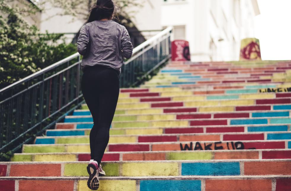 """Photo by Ev on Unsplash. A woman running up concrete stairs that have been painted bright colors, with words """"wake up""""."""