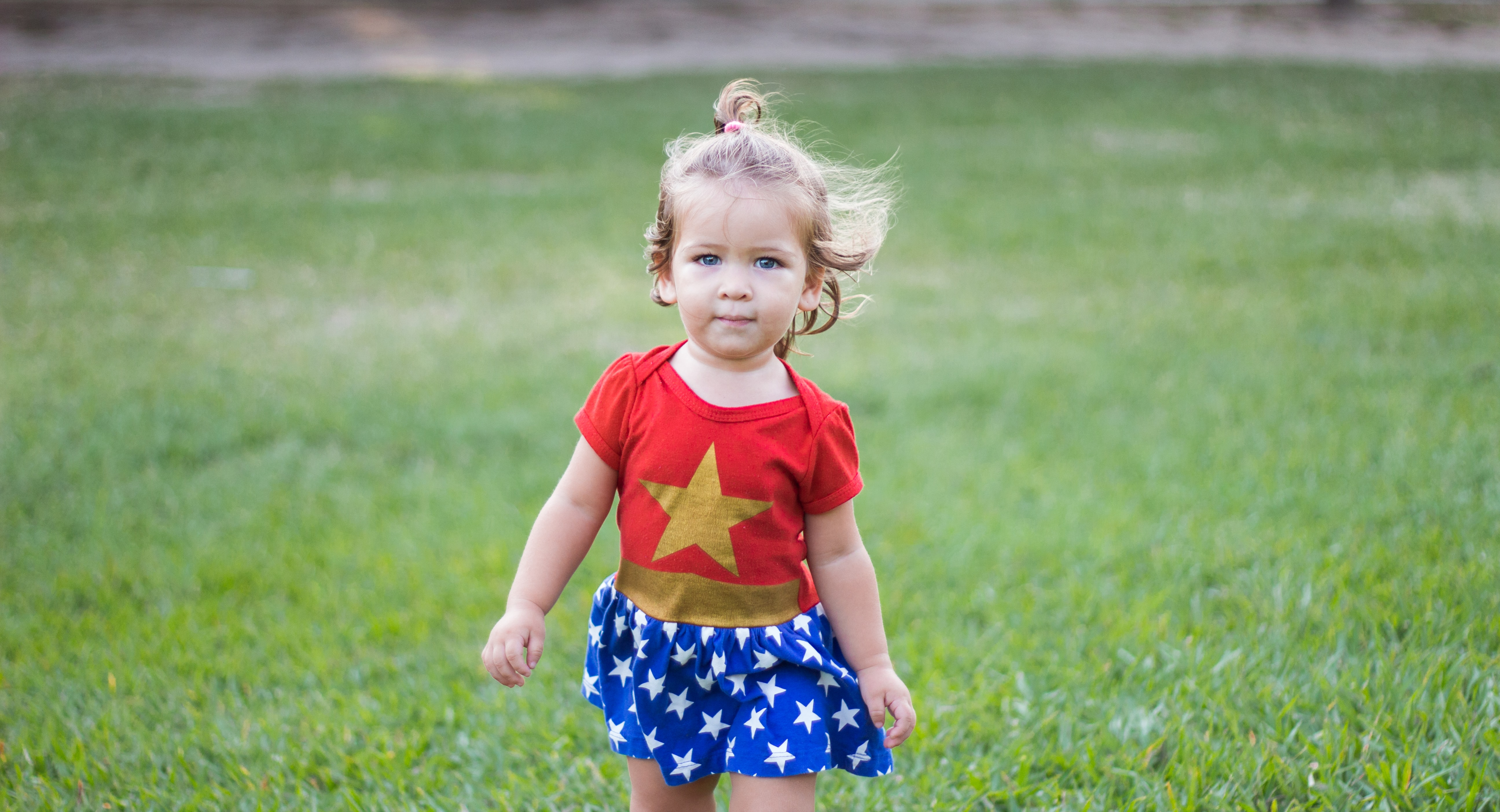 A little girl in a Wonder Woman outfit, with a big gold star. Photo by Gabriela Braga on Unsplash.