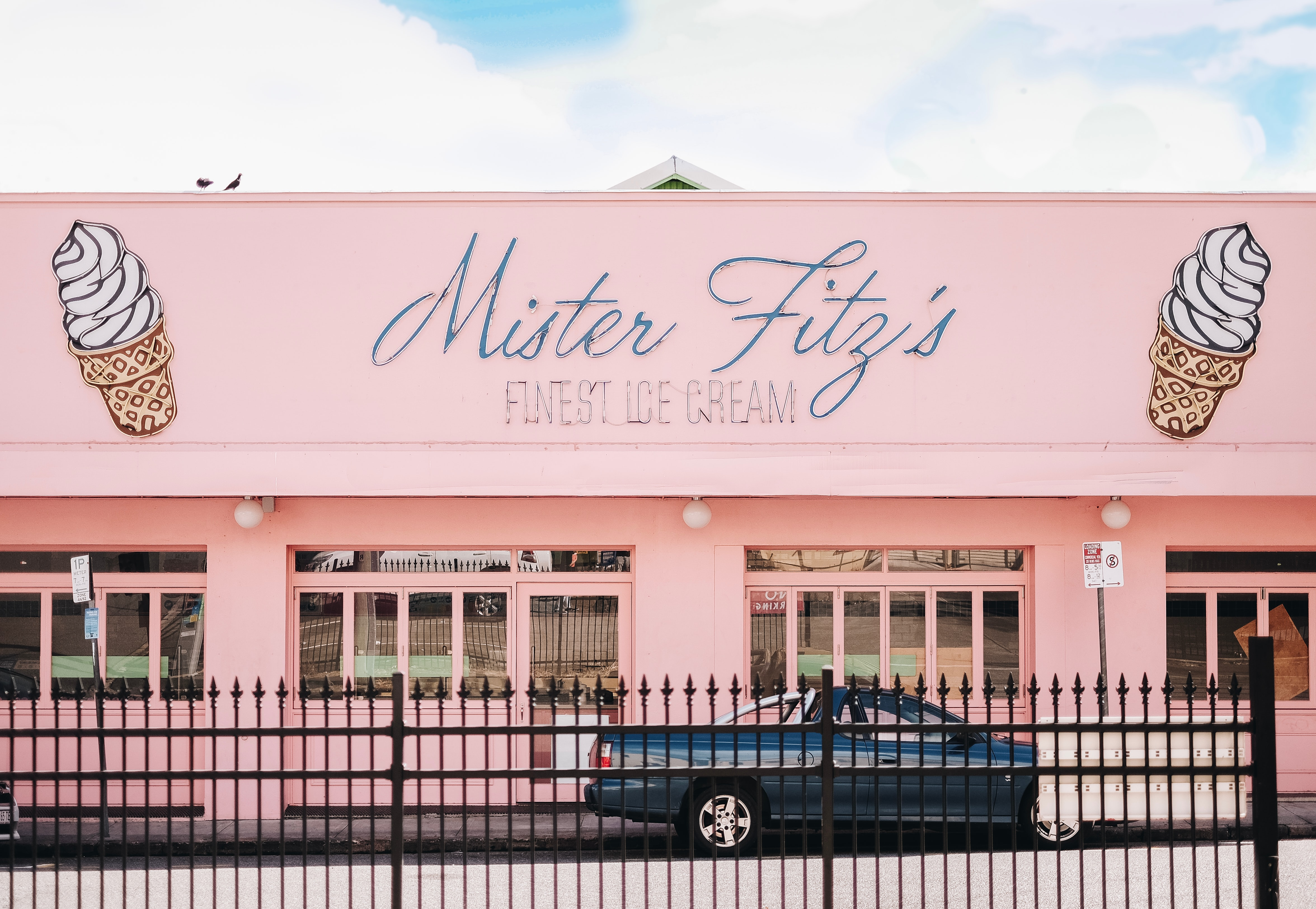 """When I typed in """"fortitude"""" to Unsplash, this came up. It's a picture of Mister Fitz' ice cream place-- the building is bubblegum pink! I hope Cate likes it. Photo by Handy Wicaksono on Unsplash."""