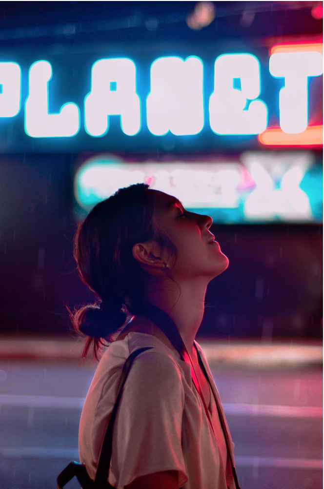 "Savoring.. by McJames Gulles, on Unsplash. A woman in a beige crew neck t shirt, looking happy. A neon sign saying ""planet"" is behind her. It's night time."