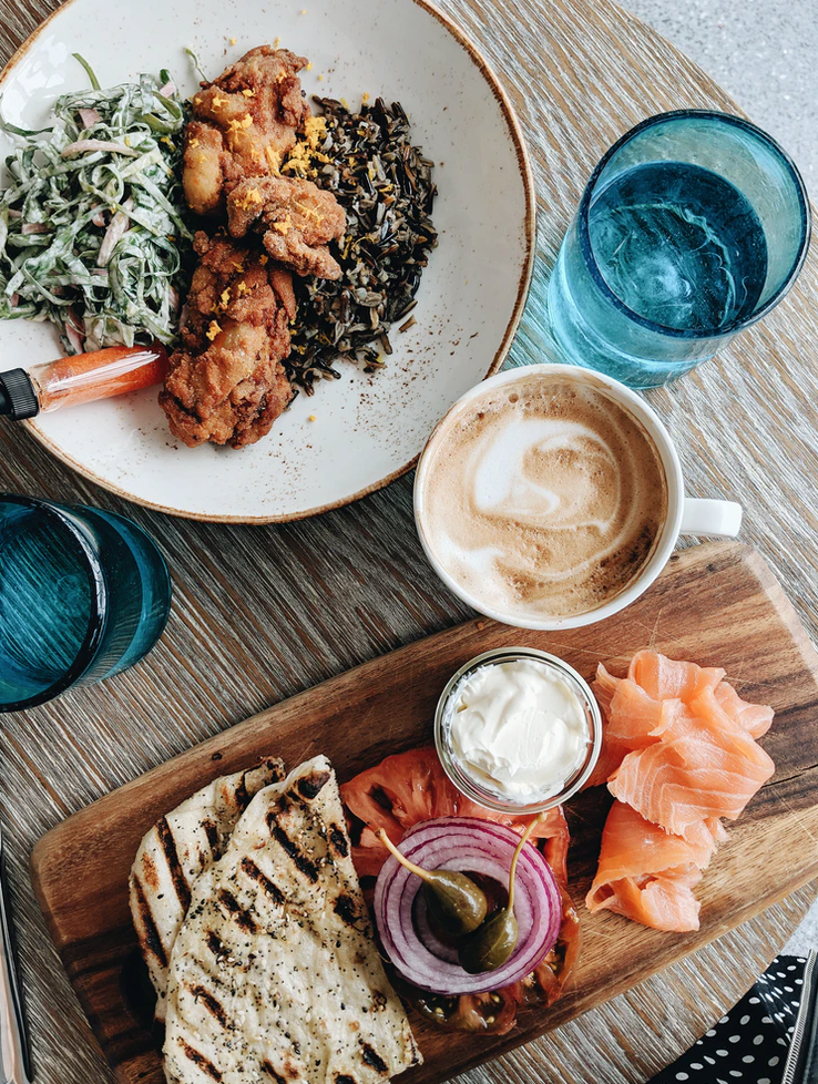 A sumptuous offering of flatbread, yogurt, olives, salmon, and other yummy items, with a latte in the middle. By Juliana Malta, for  Unsplash.