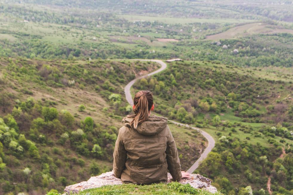A woman on a hill, looking at a winding road. Photo by Vlad Bagacian on Unsplash