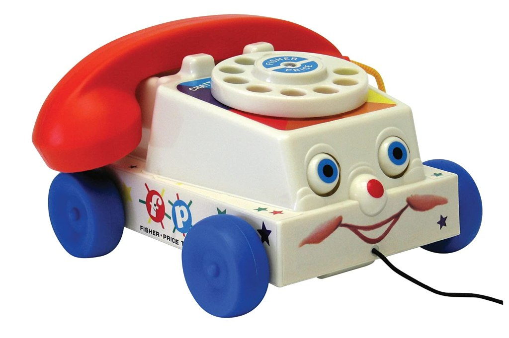 A picture of a Fisher Price telephone toy with an old time circular dial and a cute face on the front.
