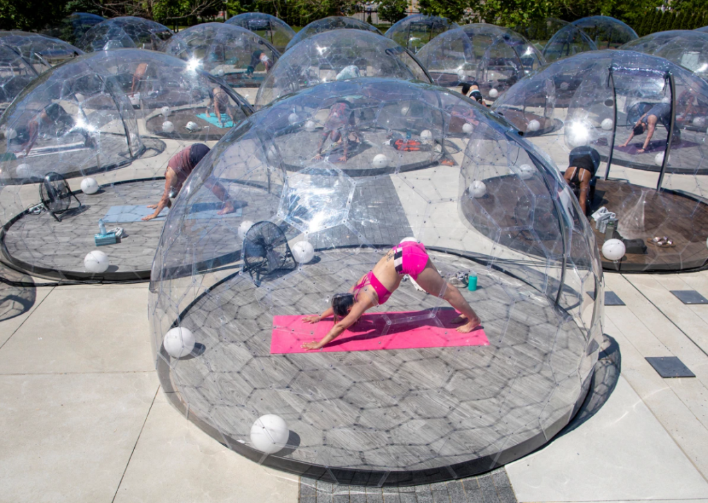 A person doing yoga (downward facing dog) inside a clear geodesic pod. In a group of others doing same. Outside. In Toronto.