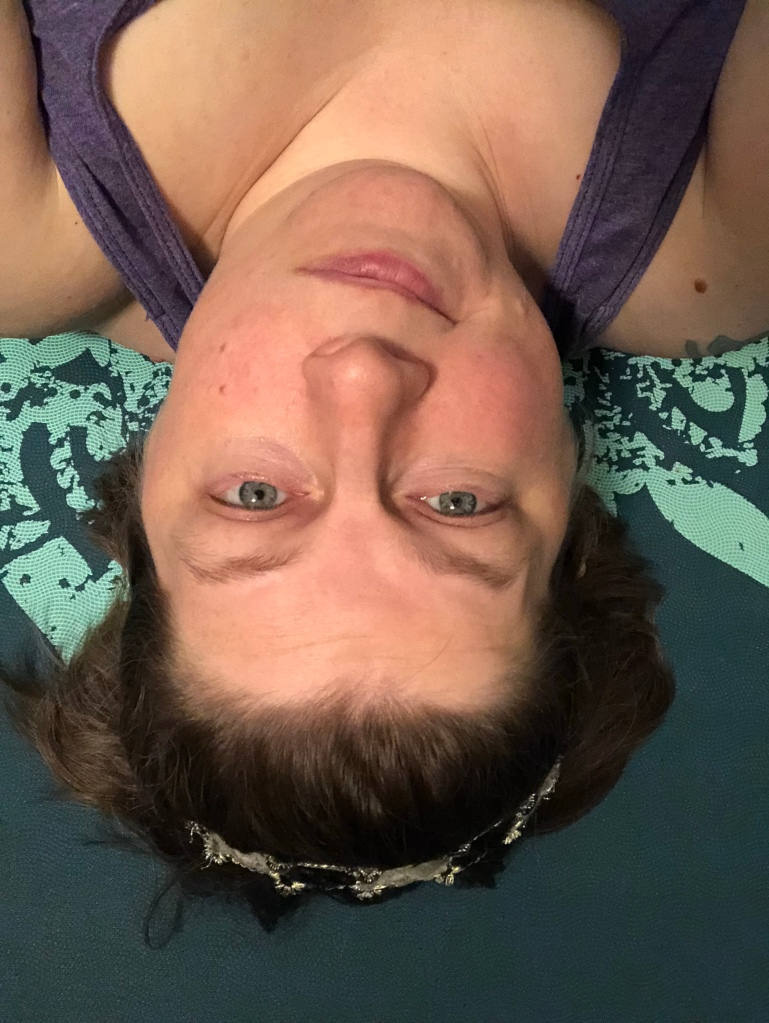 An  upside down photo of the author's head and shoulders.  She is lying on a greenish-blue yoga mat  and she is smirking in a friendly  way.