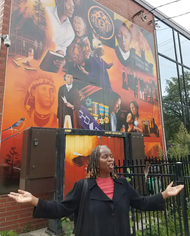 Jacqueline Scott in front of a mural in Toronto, talking  about Black History.