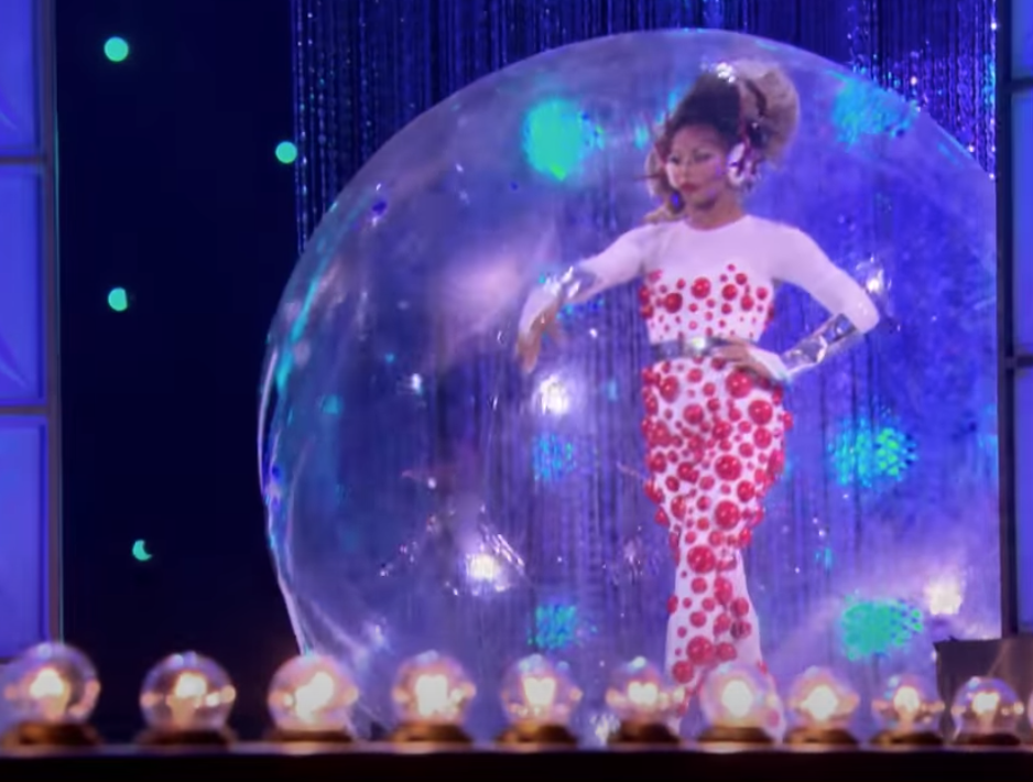 Shangela stomping the runway inside a clear plastic ball.