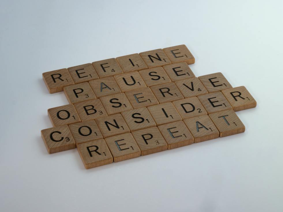 Scrabble pieces spelling, refine, pause, observe, consider, repeat. By Brett Jordan for Unsplash.