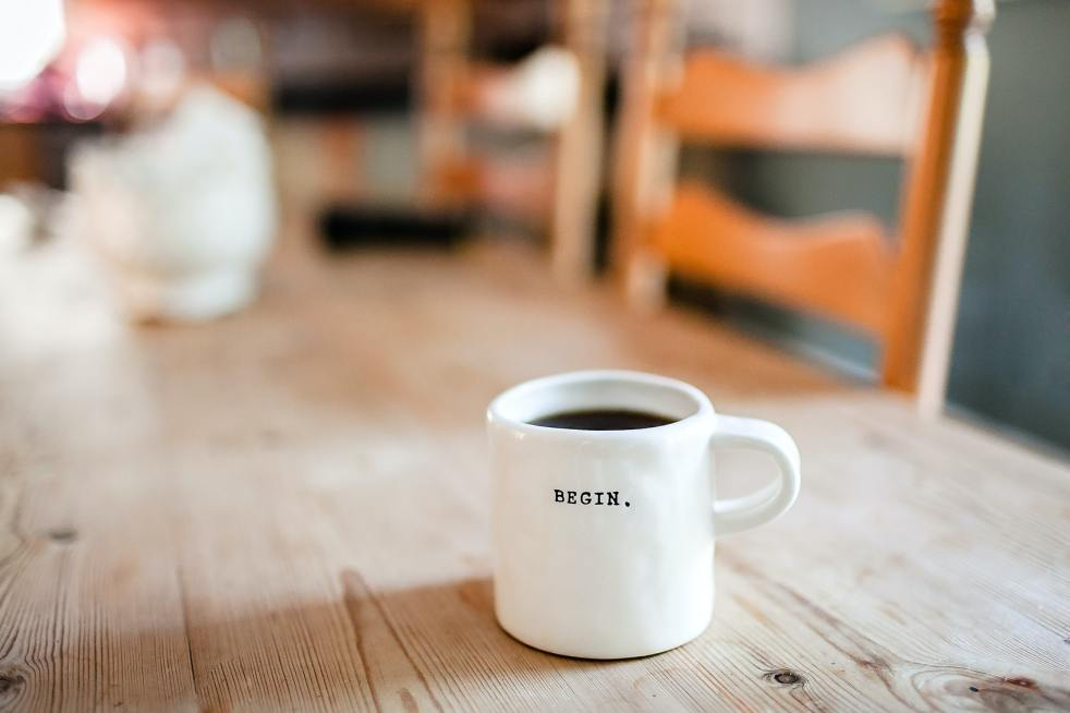 Coffee mug with message Begin. By Danielle MacInness for Unsplash.