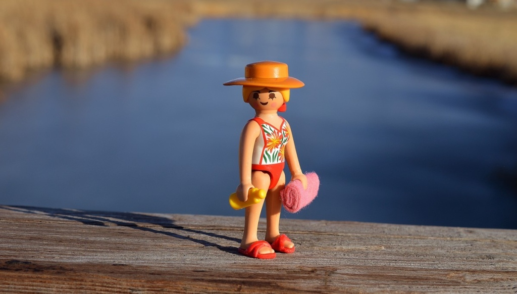 A small figurine stands on a wooden dock holding a bottle of sunscreen and a towel.