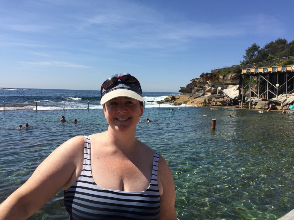 The author in a striped bathing suit in Australia, at a rock pool in Sydney.