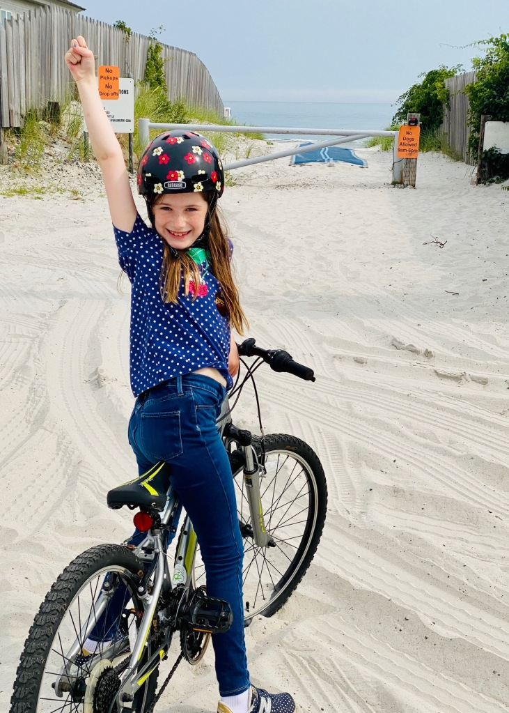 Maggie 2.0, at the beach, triumphant about her two-wheeled power.