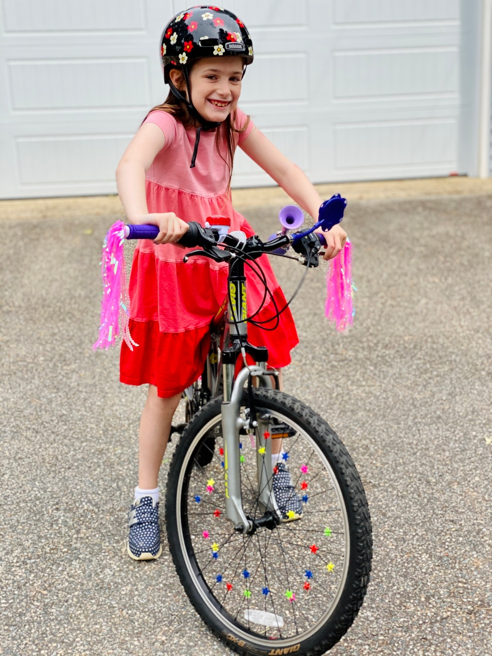 Maggie in a pink and orange dress, on a bike with pink streamers.