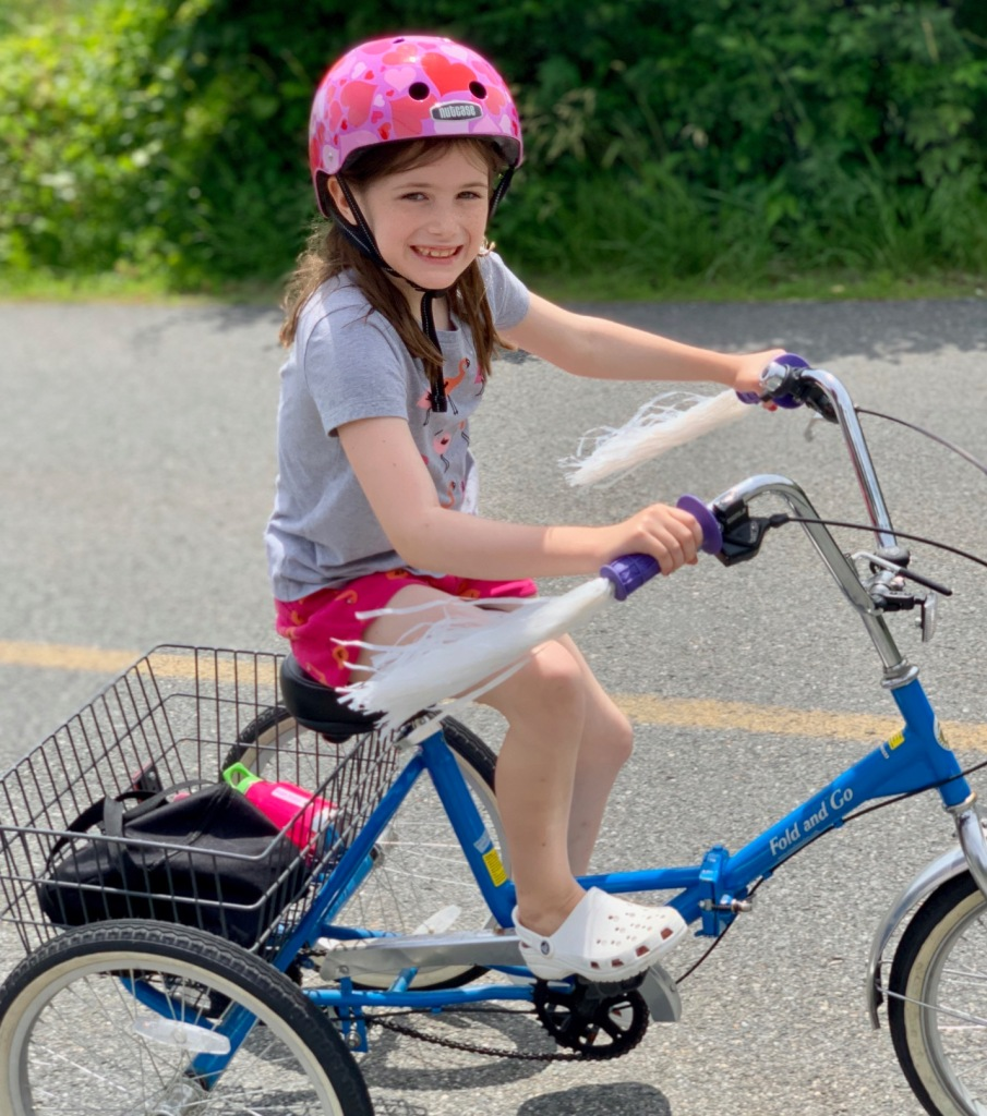 Maggie 1.0, on her three-wheeler with basket and pink helmet.