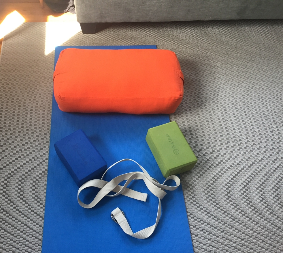 My blue yoga mat, orange bolster, a blue and green yoga blocks, with a yoga strap, in my living room.