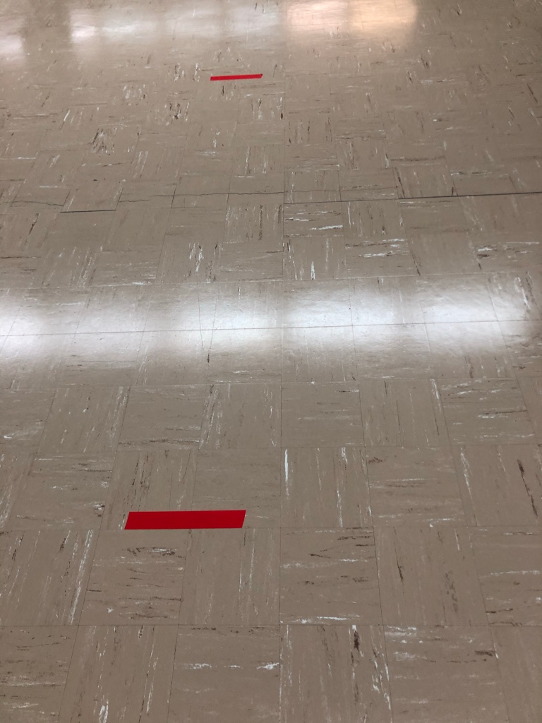 A photo of beige flooring with two pieces of red duct tape  approximately  2 m apart from each other.