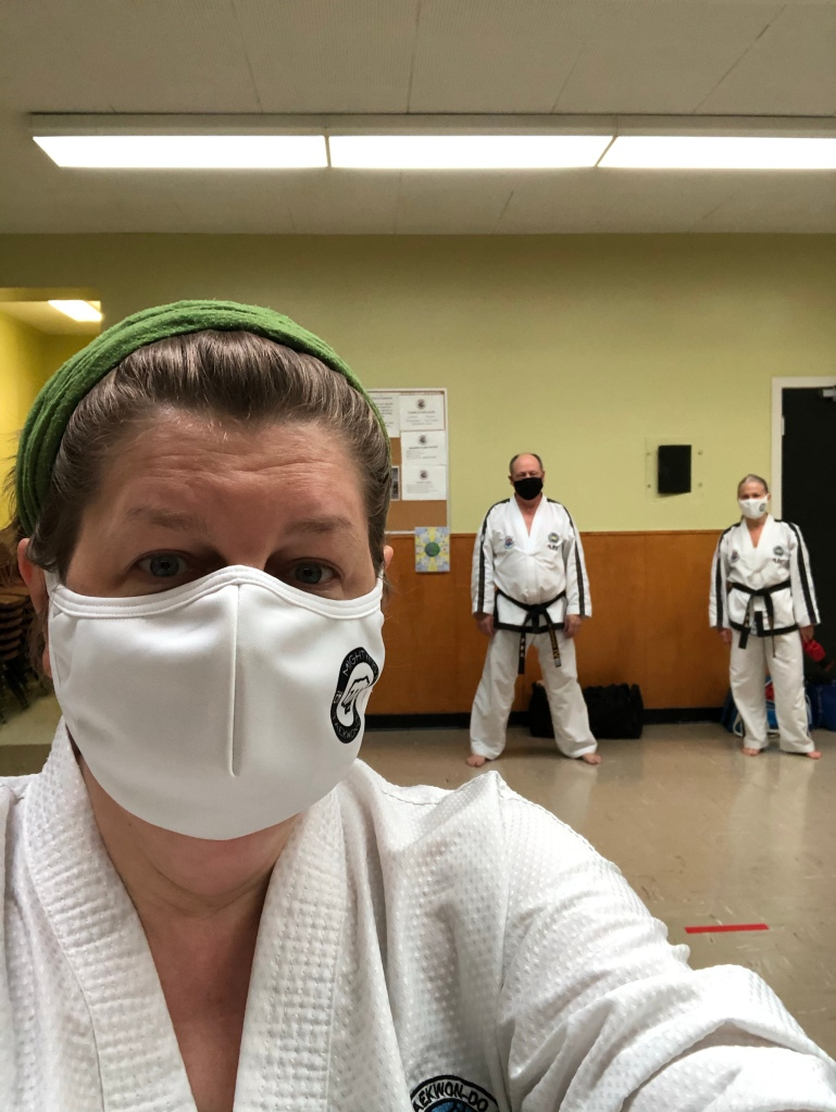 A selfie by the author. She is wearing a white dobok (martial arts clothing) and a white mask and her hair is pulled back in a bandana.  Two masked people   in doboks are far away in the background.