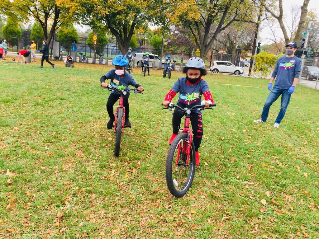 Two kids riding their bikes on grass.