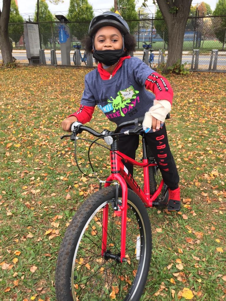 Happy kid on a red bike.