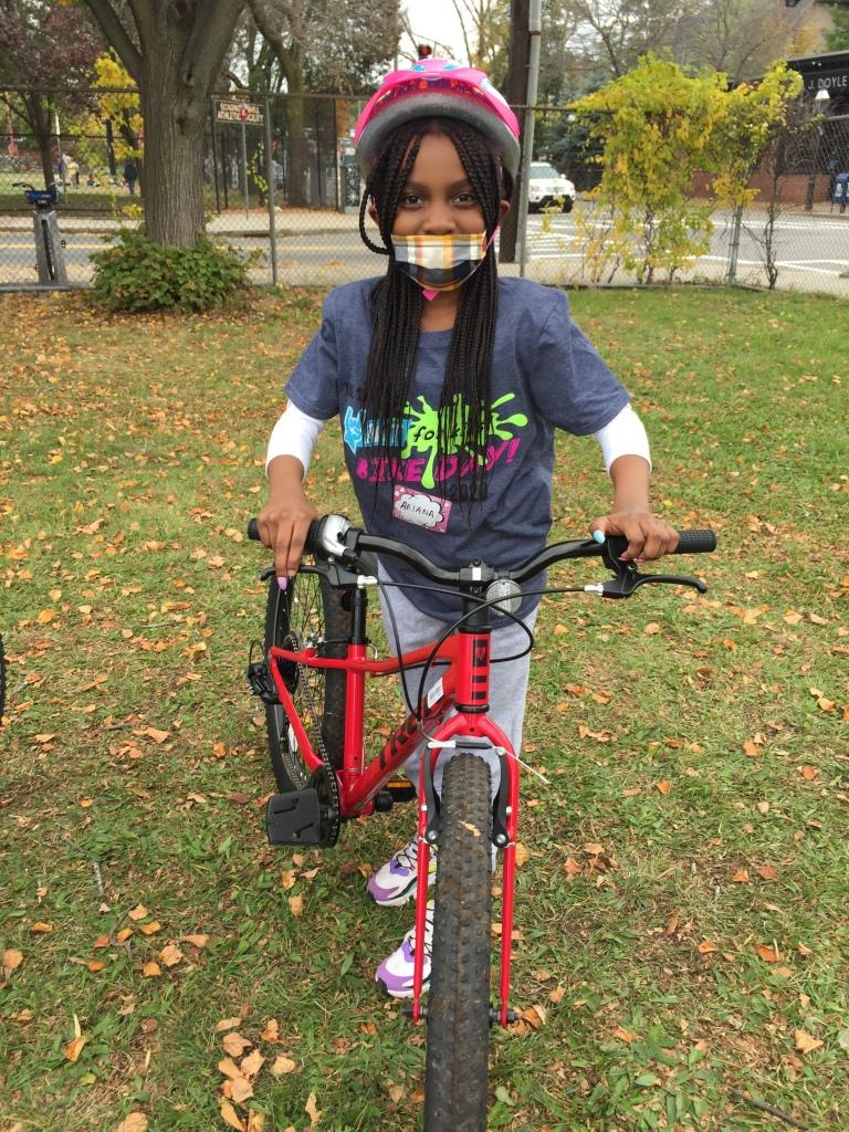 Smiling kid beside a red bike.