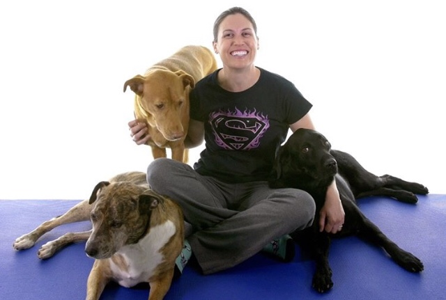 Dr. Jo,   a woman with dark hair  who is wearing a dark-coloured Supergirl  T-shirt.  She is surrounded  by three  large dogs, one black and two brown.