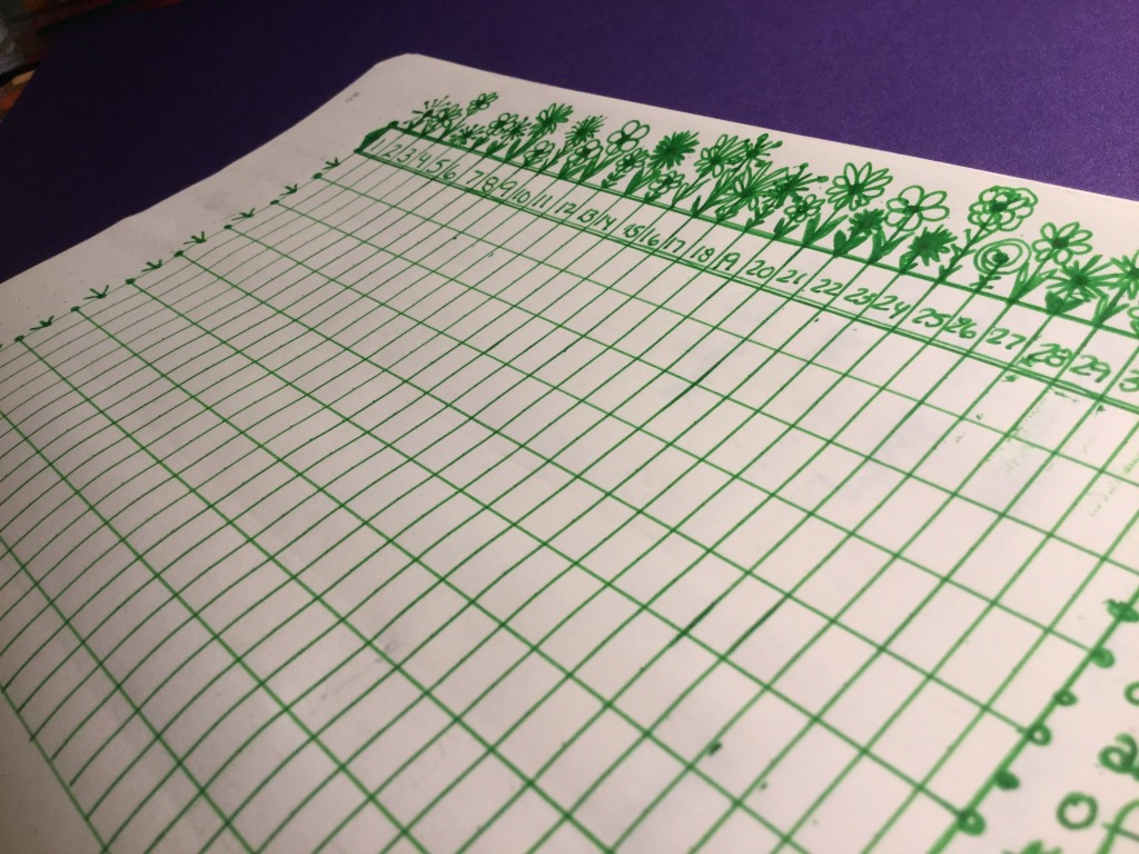 A grid is drawn in green ink on off-white paper. There are numbers in the top row and there are flowers drawn above the top line of the grid.