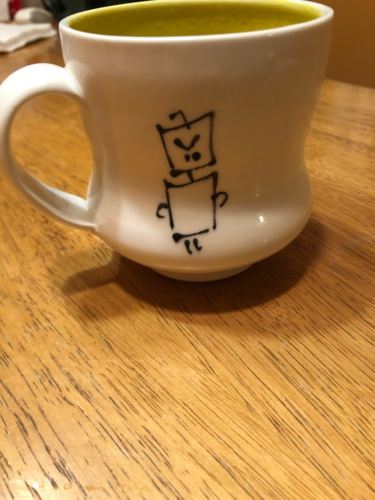 A white mug with a yellow interior   and a drawing of a grumpy  robot on the front is sitting on a wooden table.