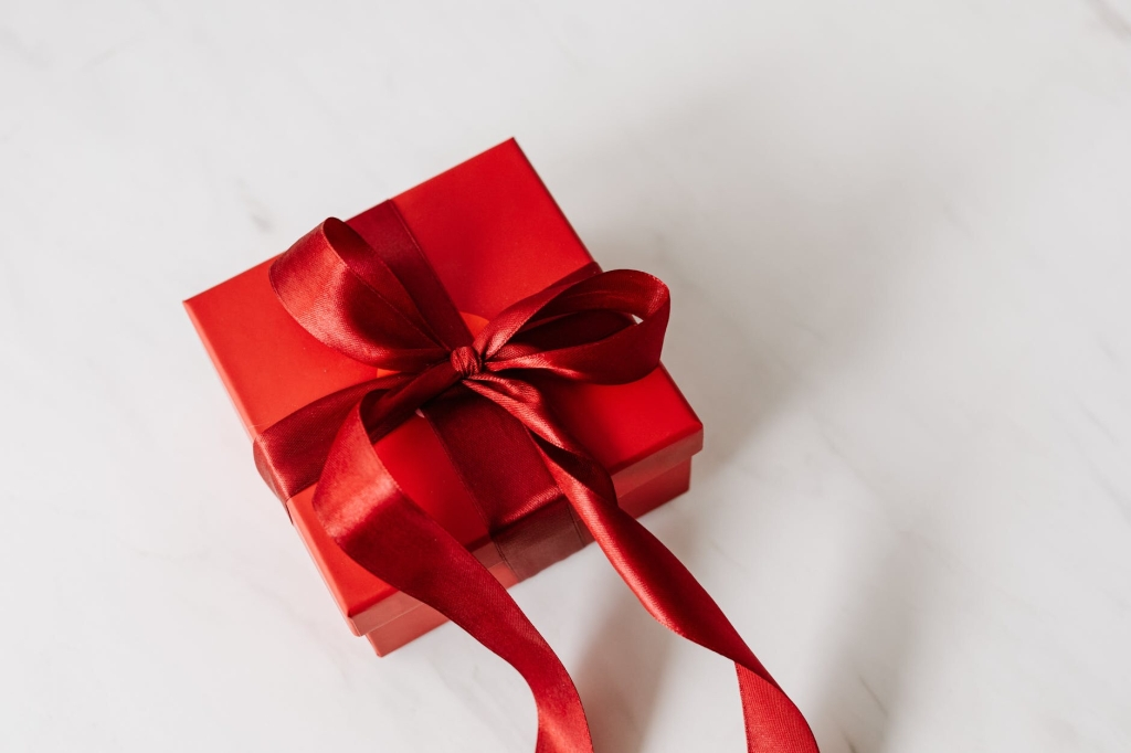 A square present is wrapped in red wrapping and tied with a large red bow.