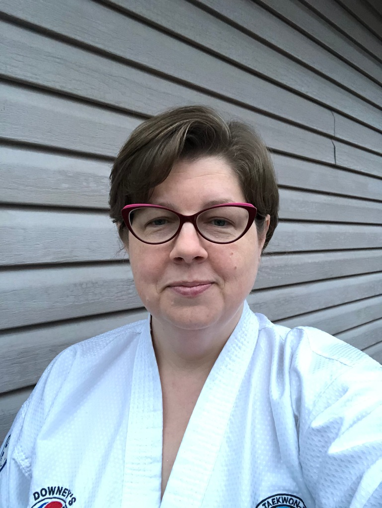 The author, a white woman in her late forties with light brown hair, stands next to an outdoor wall. She is wearing a white dobok and red-framed glasses and she is smirking slightly and she looks a bit tired.