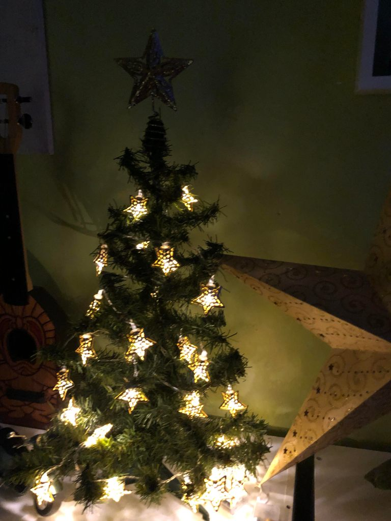 A small, green, holiday tree is sitting on a white shelf. It is decorated with gold star lights and has a gold star topper. Two points of a large cardboard star can be seen to the right side of the photo and part of a ukulele decorated with the image of a Polynesian-style statue can be seen to the right.