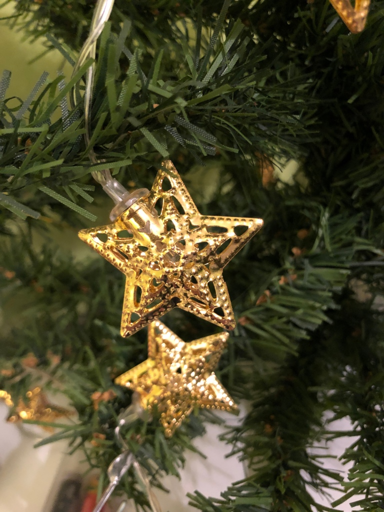 A close-up of wo  gold-coloured star-shaped lights  hanging on the branches of an artificial Christmas tree.