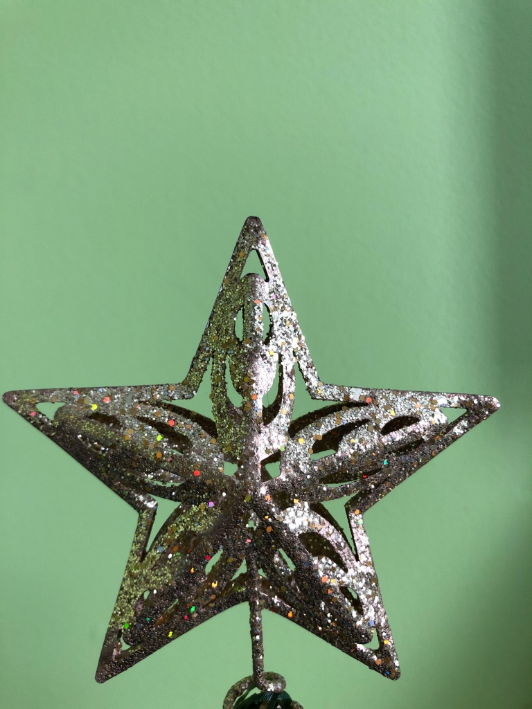 Image description: A sparkly gold star decoration stands in front of a light green wall.