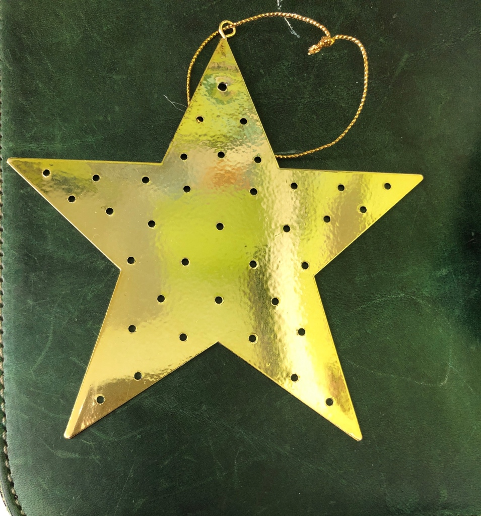 Image description - a gold star shaped decoration that is dotted with holes and has a gold string attached rests on a scratched green leather surface.