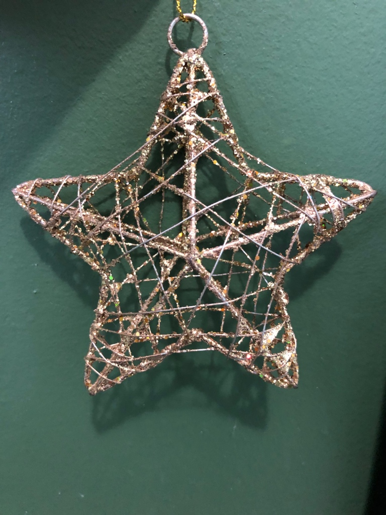 A woven gold star rests against a dark green wall.