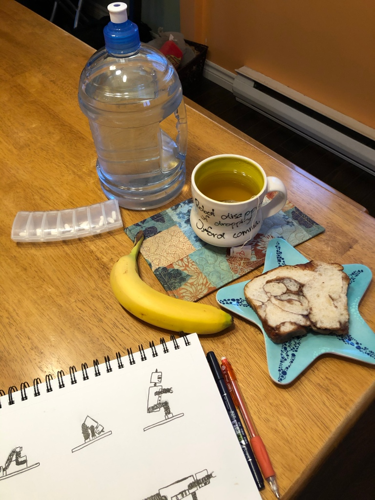 The photo shows my giant water bottle, a white mug (with yellow interior) containing ginger tea, a banana, a slice of cinnamon bread on a star-shaped plate, a week-sized pill-sorter, and a notebook opened to a white page covered in sketches of robots in yoga poses. A pen and pencil sit next to the notebook.​