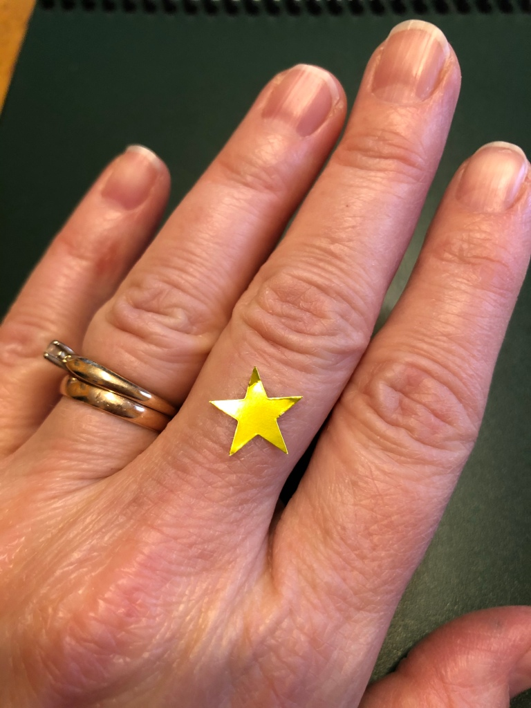 A photo of the author's left hand.    She  has two gold rings on her ring finger and there is a  gold star sticker on the back of her  middle finger between the second knuckle on her finger and the knuckle on the back of her hand.