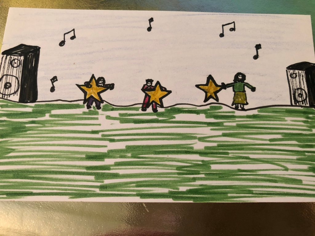 Image description: An index card drawing of ​three tiny people holding gold stars almost as large as they are. They are standing on a green field with stereo speakers at either end and there are music notes in the air above them. The index card is resting on a shiny gold surface.