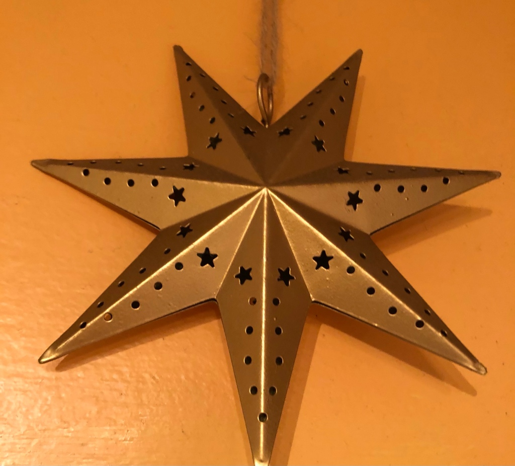 Image description: a gold star decoration covered in cut-out dots and stars hangs on an orange wall. The photo is taken from slightly underneath the star.