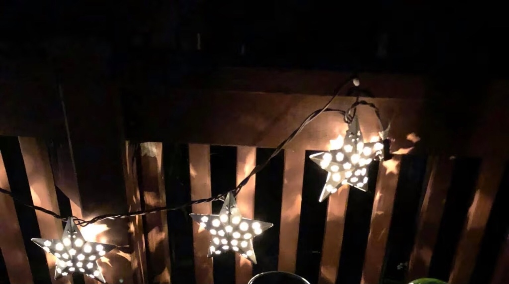 Image description : Three star shaped patio lights hang on a railing at night. The light of each one is shining through multiple star​-shaped holes on the sides of the larger star.